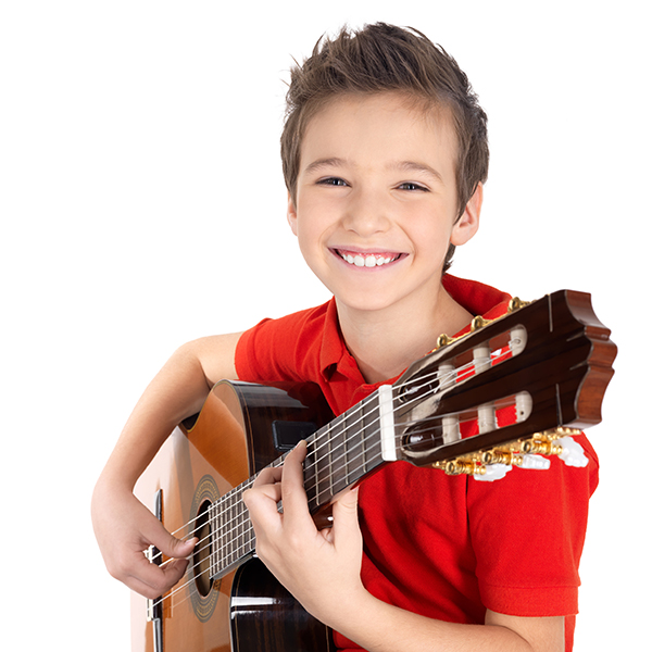 Happy boy is playing on acoustic guitar - isolated on white background